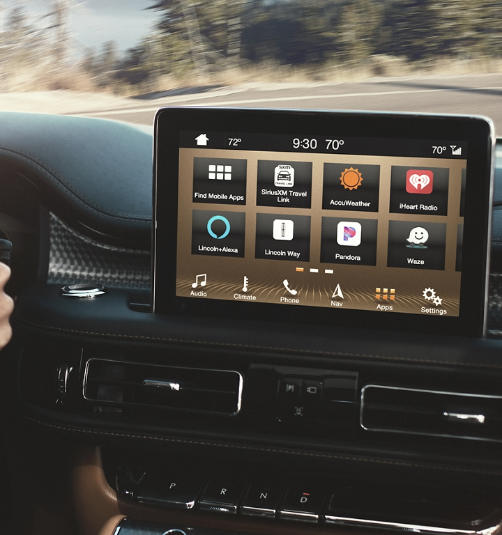 A hand is shown using the at home charging station for the Aviator Grand Touring model