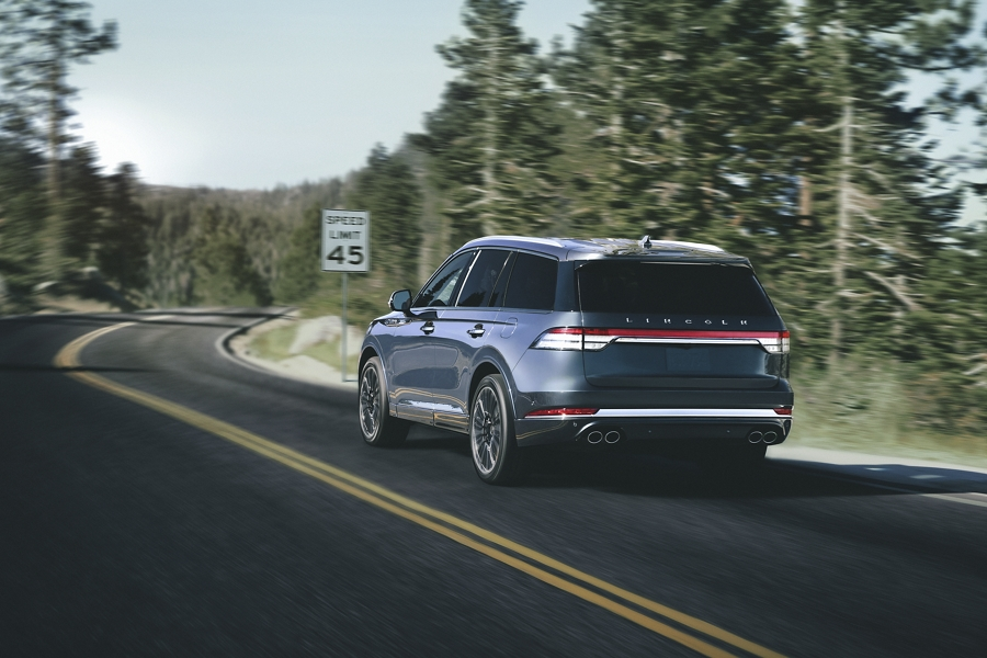 A Lincoln Aviator is shown driving on a road as it approaches a stop sign to highlight a number of driver assist features