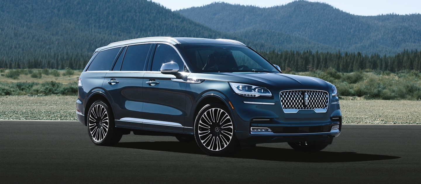 A Lincoln Black Label Aviator shown in the Flight Blue exterior color is parked on pavement with mountains in the background.