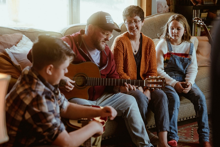 Cas sharing new songs on the guitar with his family.
