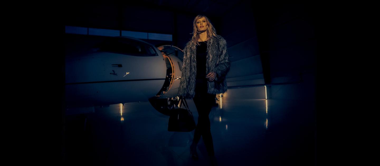 Imagen de una mujer que se aleja de un avión privado de noche