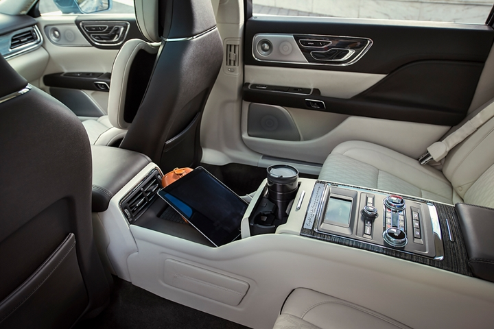 Lincoln Continental Coach Door Edition rear suite console with wireless charging and tray table is shown