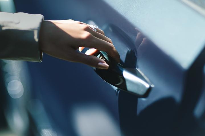 Una mano toma con gracia la manija de la puerta e latch para demostrar su uso fácil