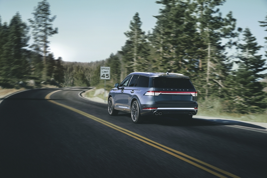 A Lincoln Aviator is shown driving on a road as it approaches a speed limit sign to highlight a number of driver assist features