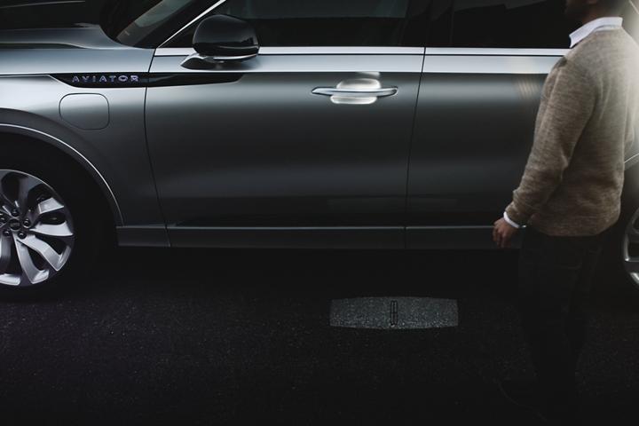 Una persona se acerca a una Lincoln Aviator mientras se ilumina la secuencia de luces de bienvenida de Lincoln Embrace