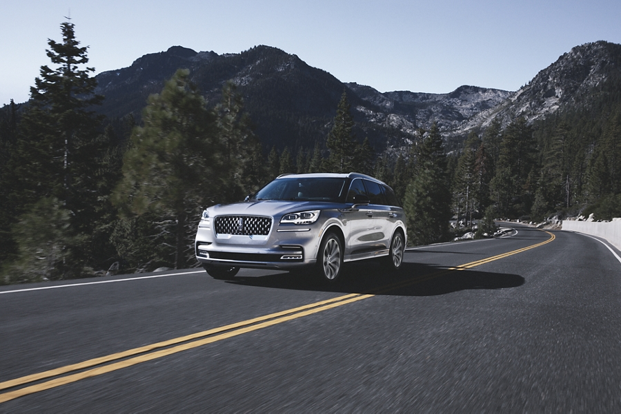 A Lincoln Grand Touring model is shown being driven through a breathtaking mountain pass