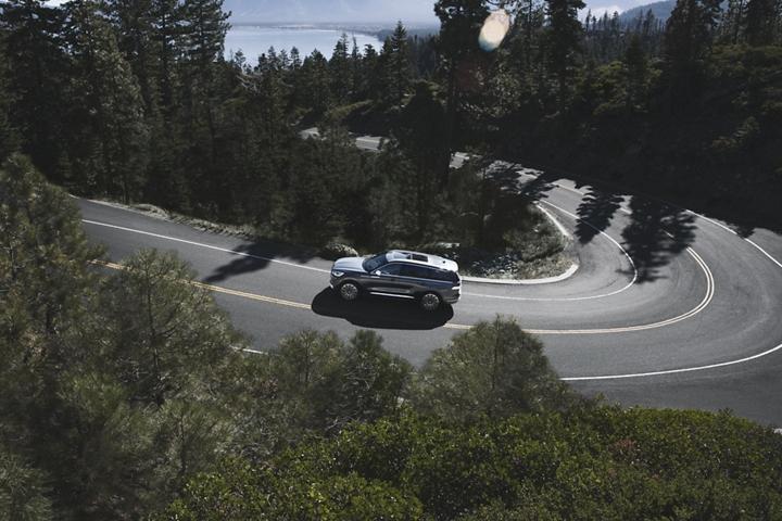 Se muestra una Lincoln Aviator desde arriba mientras pasa por una carretera montañosa serpenteante
