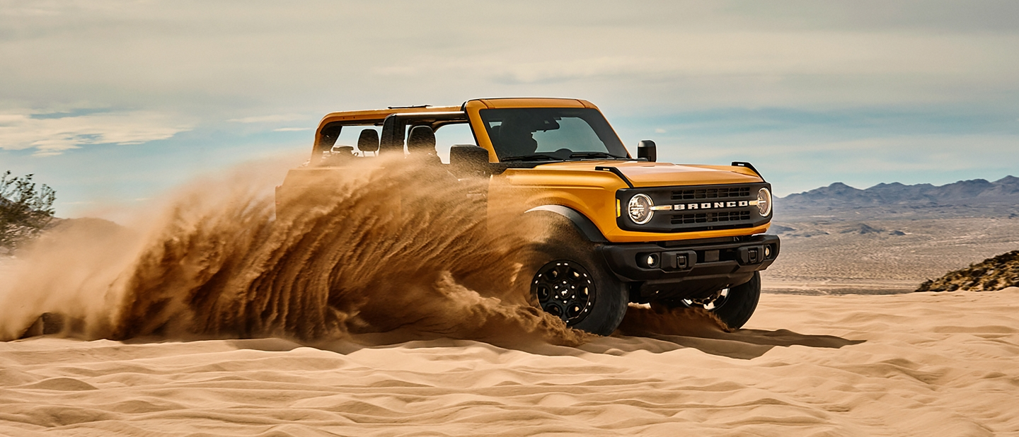 Ford Bronco driving through the sand dunes