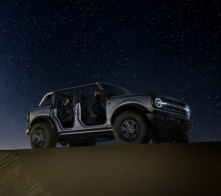 2021 Ford Bronco sitting on top of a sand dune with a starry sky backdrop
