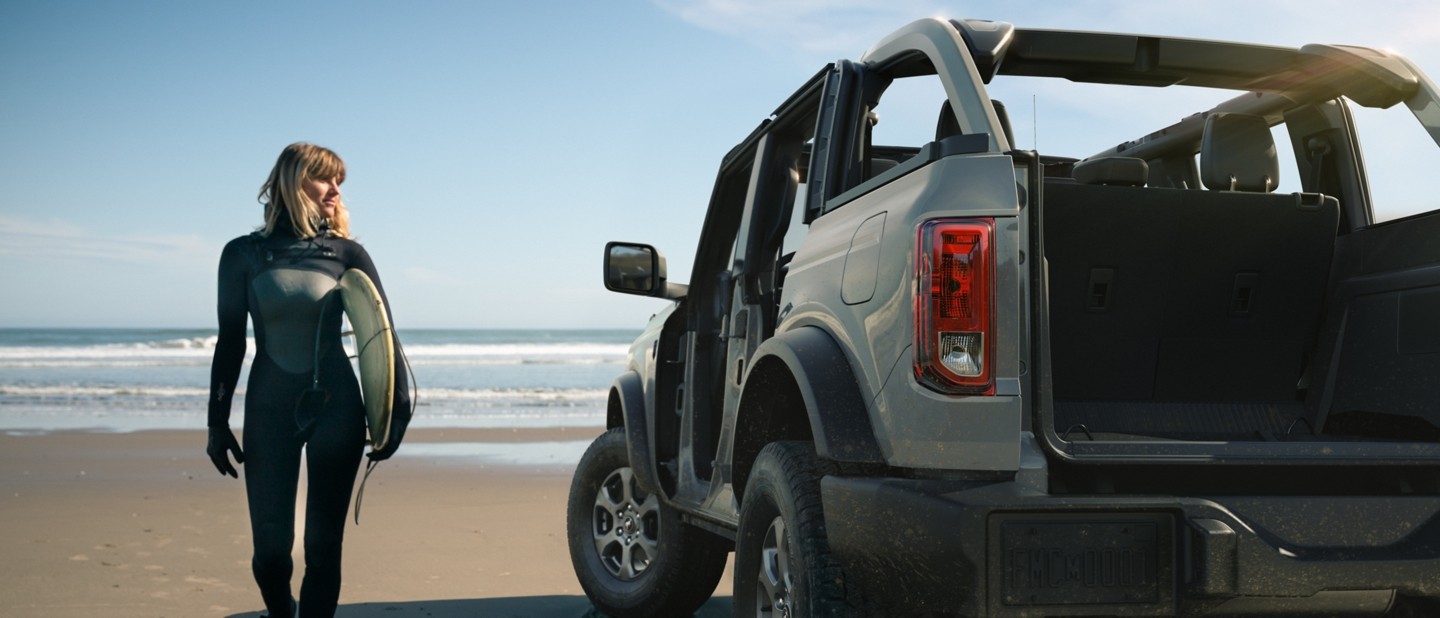 Female Surfer walking next to Ford Bronco  4 door on a beach