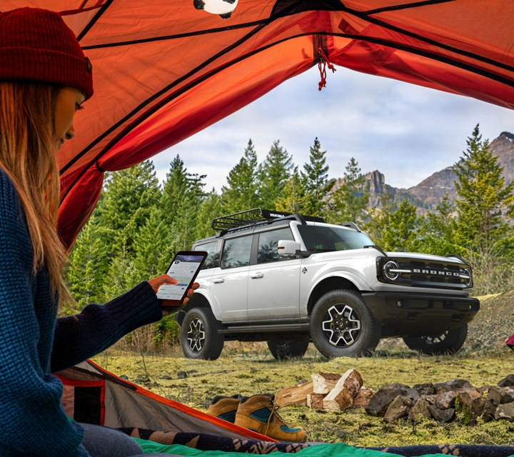 2021 Ford Bronco four door model seen through a tent with woman on her phone