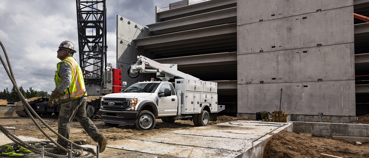 Construction worker walking near 2020 Ford Super Duty Chassis Cab with upfit at worksite