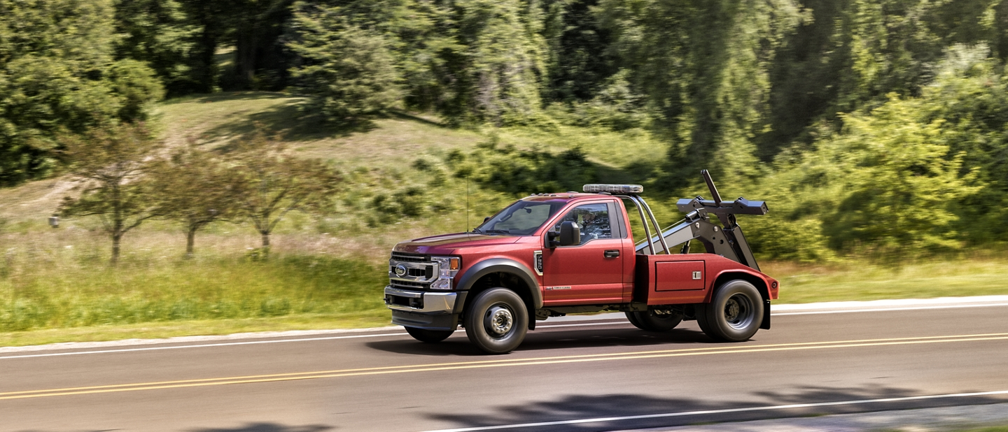 2020 Ford Super Duty Chassis Cab F 600 in Rapid Red with upfit being driven on road near trees