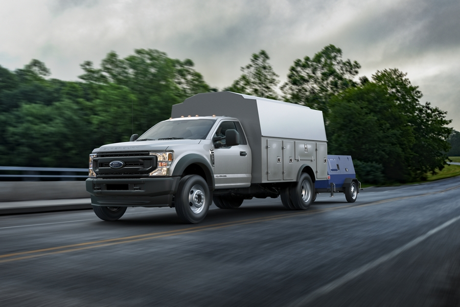 2020 Ford Super Duty Chassis Cab with flatbed body and flatbed trailer being driven on road