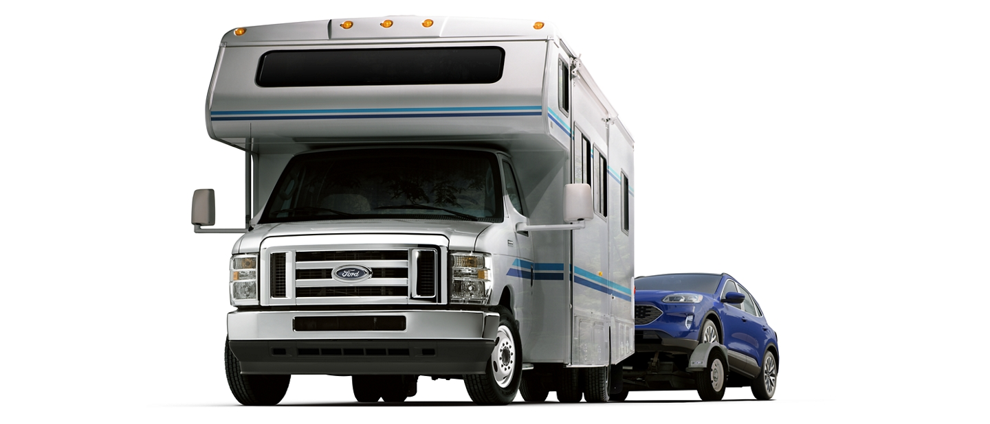The 2021 Ford E Series Cutaway with Class C Motorhome towing auto trailer
