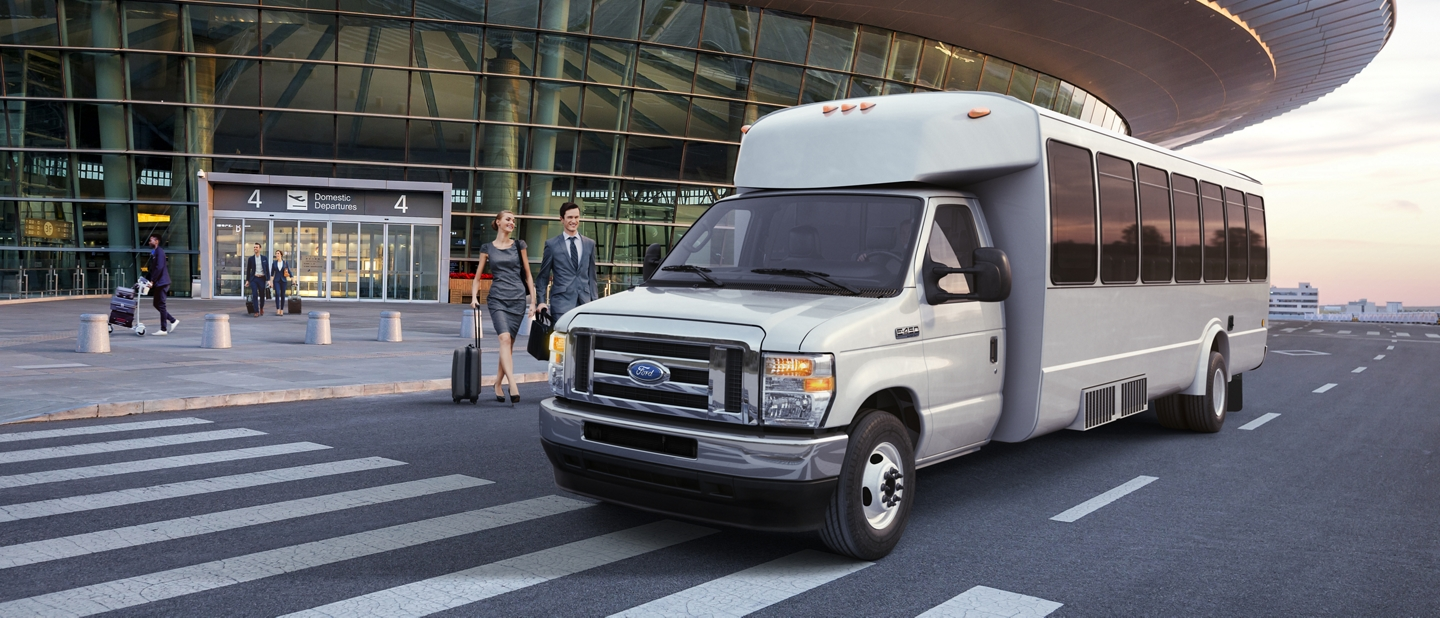 2021 Ford E Series Cutaway with aftermarket shuttle bus body parked outside of an airport