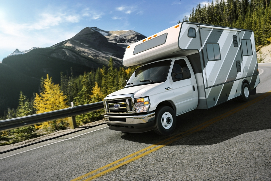 2021 Ford E Series with Class C Motorhome towing auto trailer around a curve with mountain in the background