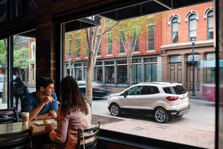 The 2019 EcoSport Titanium in White Platinum Metallic tri coat seen through a restaurant window