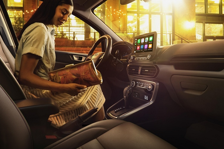 Woman entering the 2019 EcoSport with ebony black seats and a centre stack with an available eight inch touchscreen