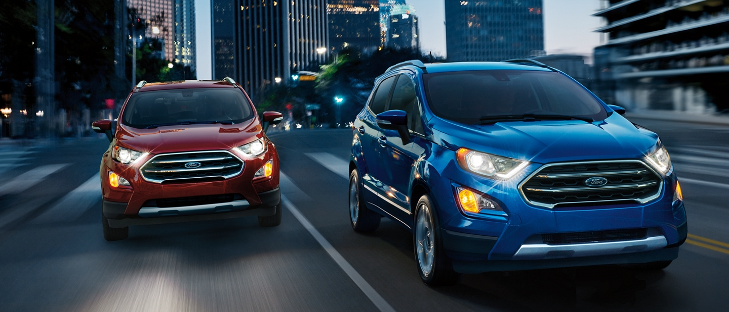The 2019 EcoSport Titanium in Lightning Blue on a city street with another EcoSport in Ruby Red about to pass on the right