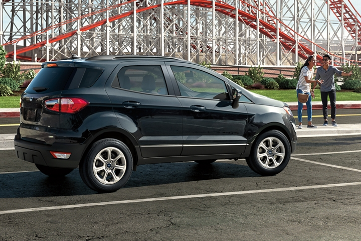 2019 EcoSport S E in Shadow Black in front of an amusement park