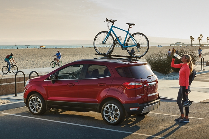 The 2019 Ecosport Titanium in Ruby Red Metallic Tinted Clearcoat with silver roof rails providing extra room for a bike