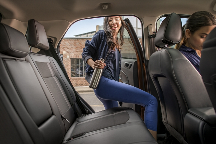 Woman getting into roomy rear seat of the 2020 Ford EcoSport