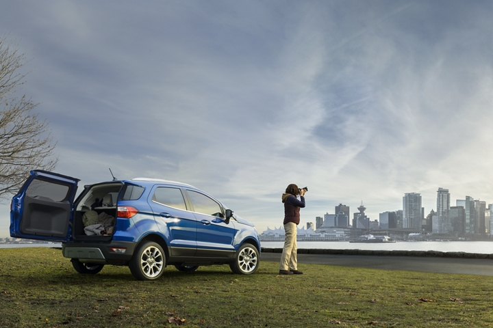 Woman taking pictures of nearby city next to the 2020 Ford EcoSport Titanium in Lightning Blue with its stylish rear swing gate open
