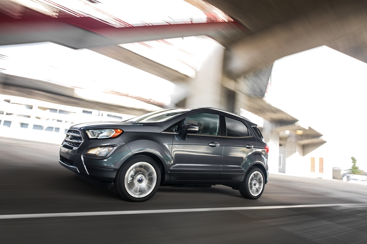 A 2020 Ford EcoSport in Smoke being driven under a bridge