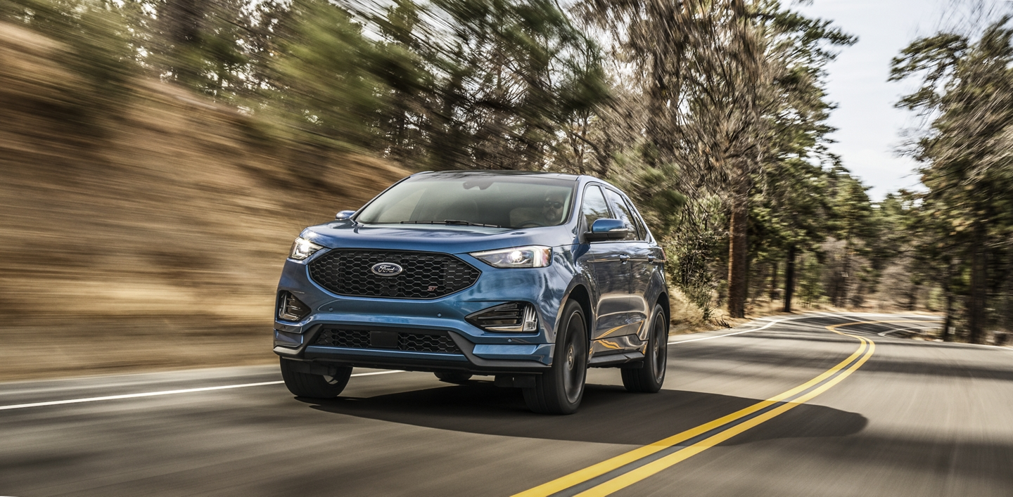 Le Ford Edge ST 2020 illustré en bleu Ford Performance conduit dans un boisé