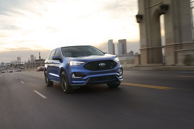 A 2020 Ford Edge ST in Ford Performance Blue being driven across a bridge