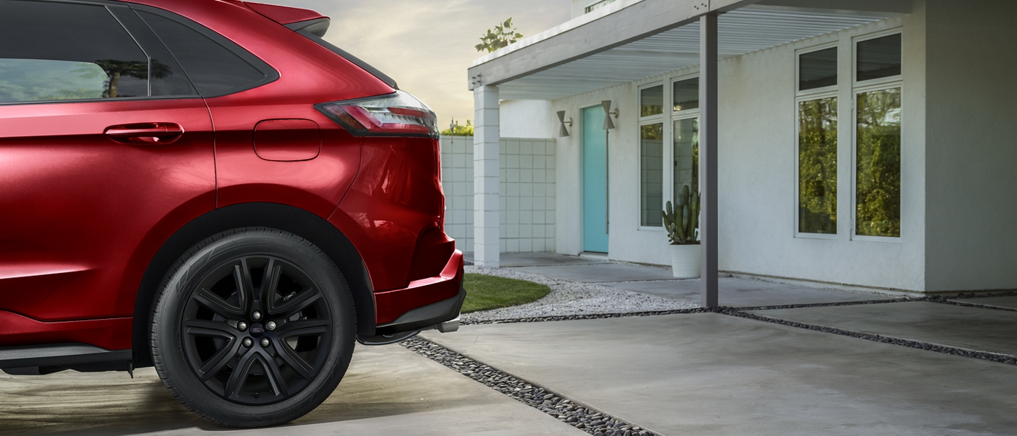 Rear of 2020 Ford Edge S T Line in Rapid Red parked in driveway at modern home