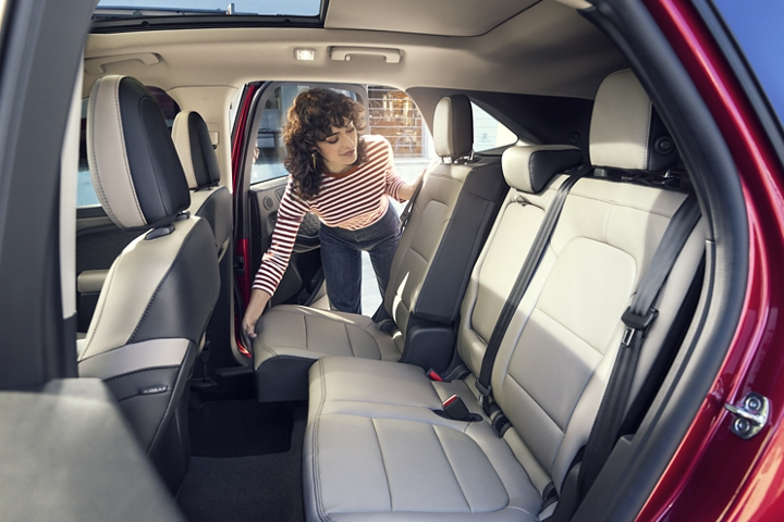 Woman shown sliding the second row seat of a 2020 Ford Escape