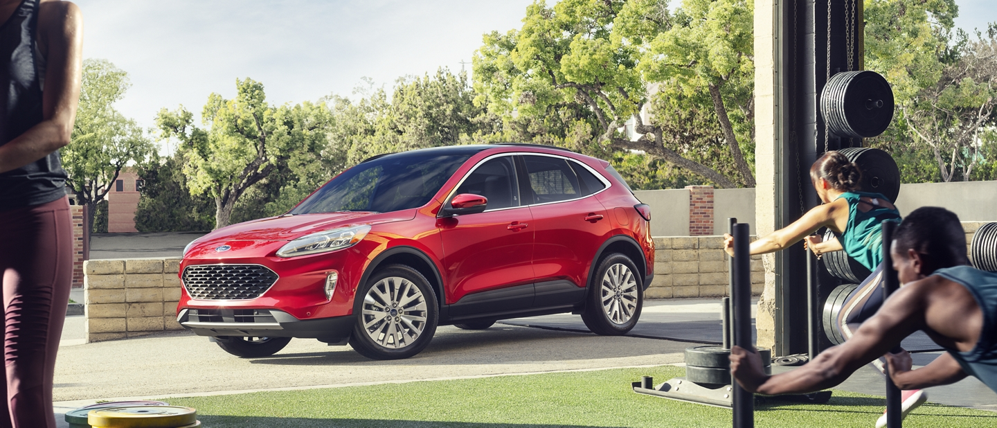 2020 Ford Escape in Rapid Red in front of a fitness facility with hotspots for features