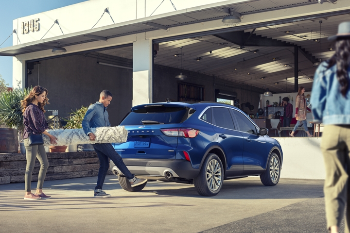 A young couple using the hands free foot activated liftgate to load their 2020 Ford Escape Hybrid Titanium