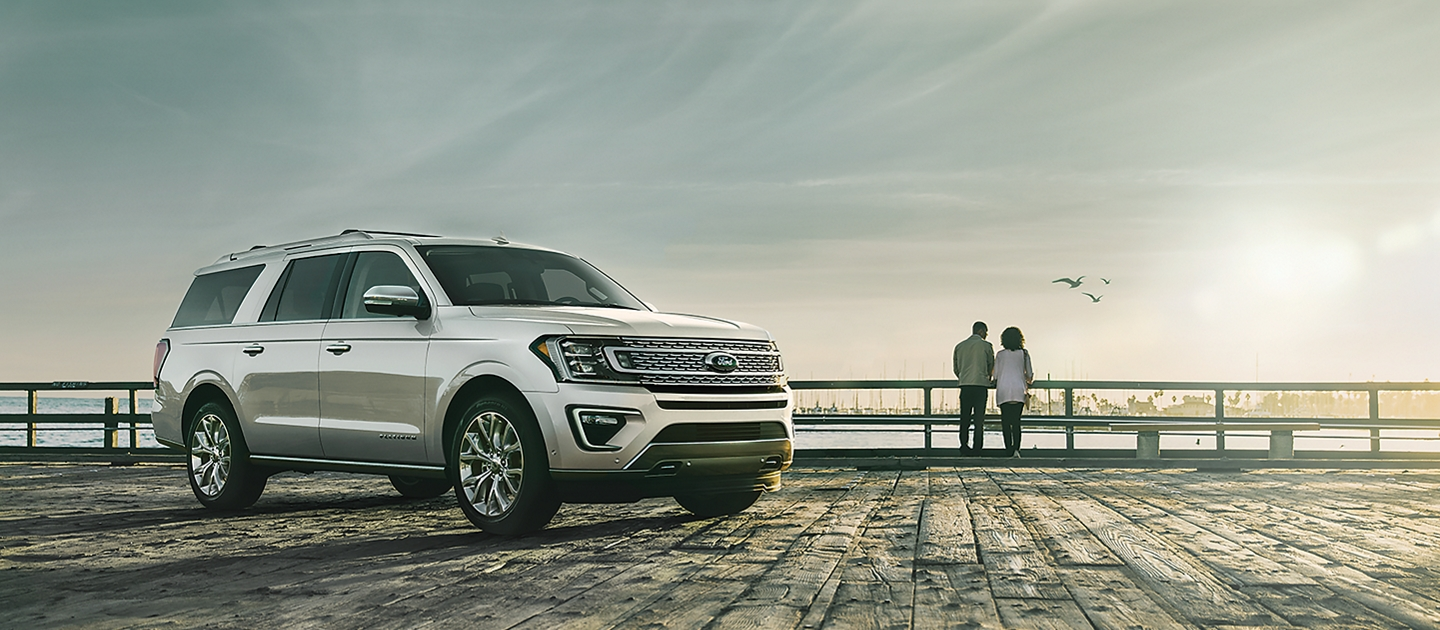 A Ford Expedition drives along a coastal highway.