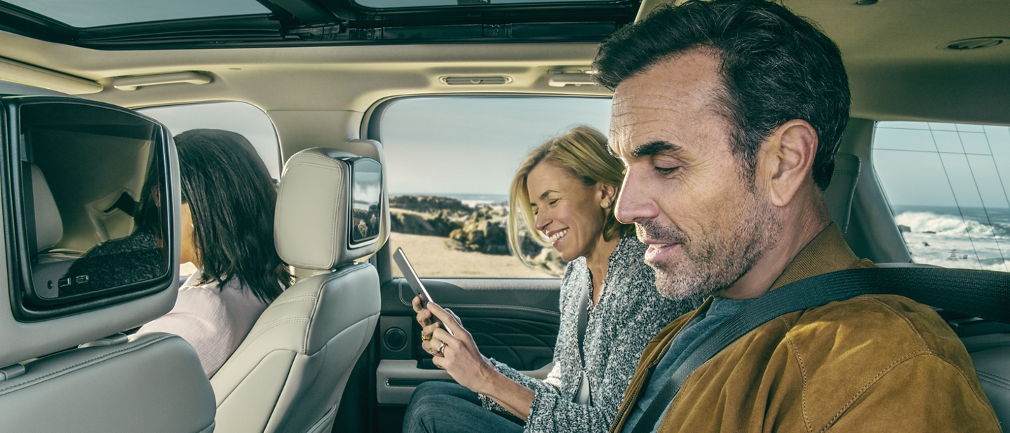 People in second row of 2020 Ford Expedition Platinum using their smartphones