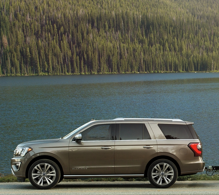 2020 Ford Expedition shown parked next to a lake while towing a boat