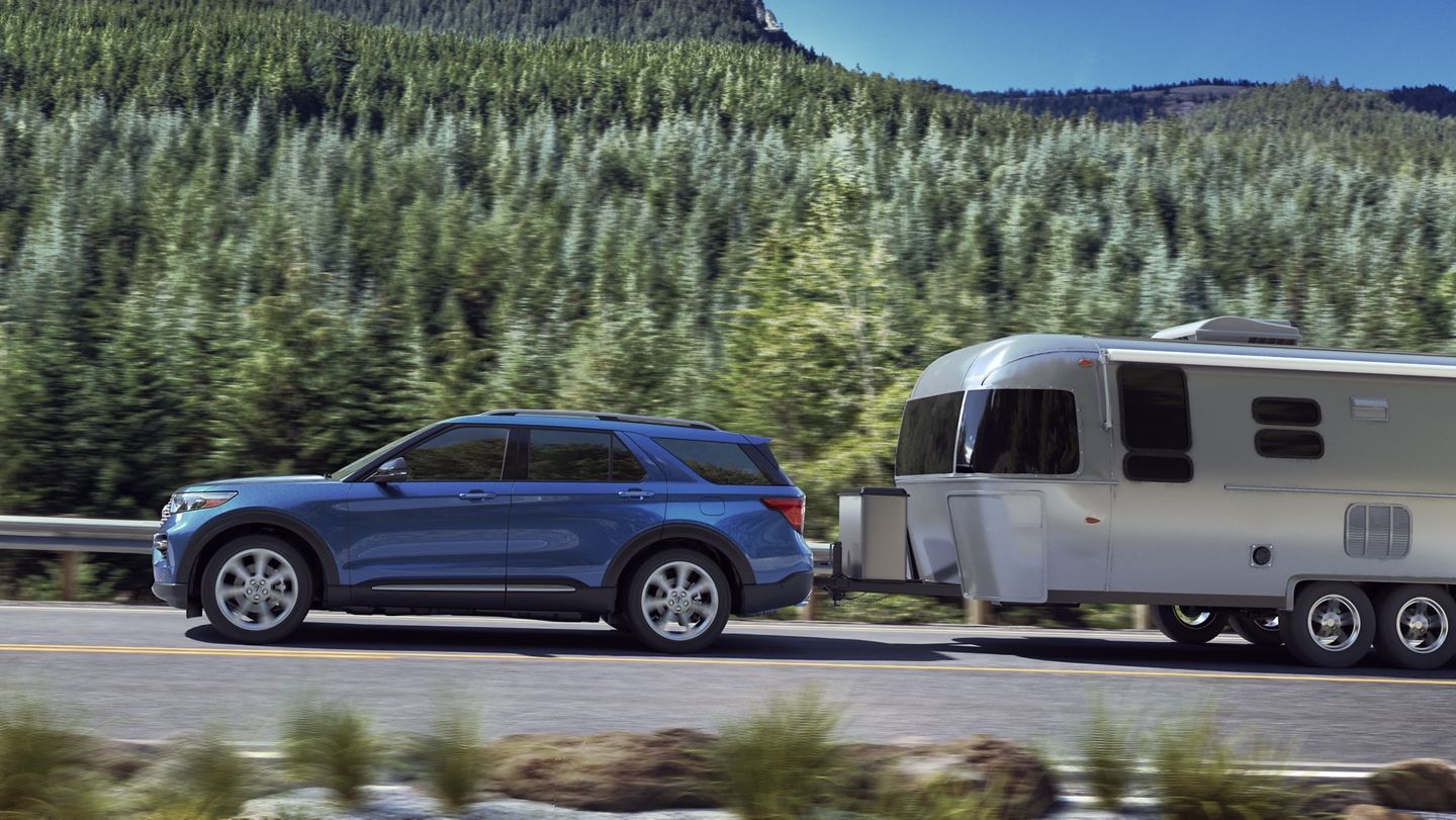 The 2020 Explorer in Atlas Blue pulls a camper on the highway