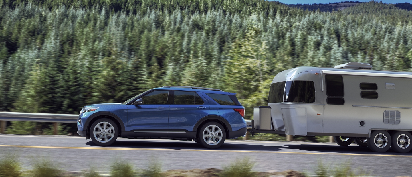A 2020 Ford Explorer Hybrid in Atlas Blue towing a camper on the highway