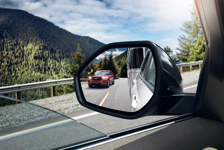 Close up of an auto dimming sideview mirror showing the reflection of a 2020 Explorer in Rapid Red