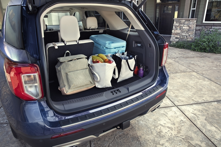 A 2020 Explorer with the rear door open to show cargo space filled with groceries and a cooler