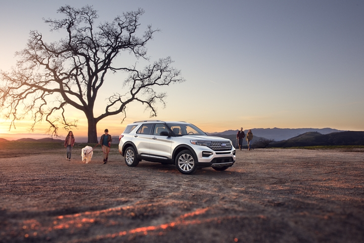 A family walking toward an Explorer Limited in Star White parked at the top of a mountain