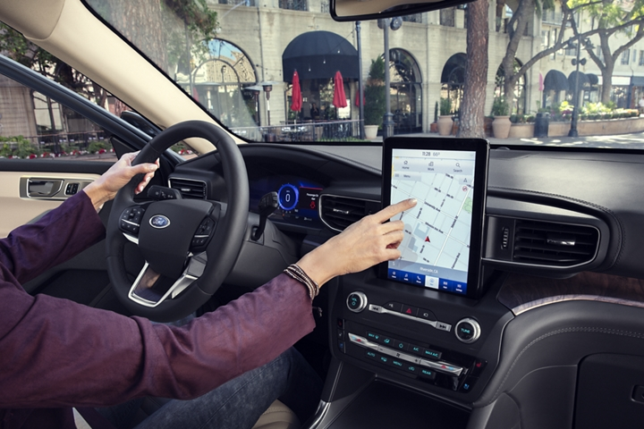 A person in the drivers seat of a 2020 Explorer using the ten point one inch L E D touchscreen
