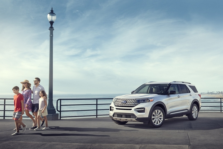 A family walking away from a 2020 Explorer Limited in Star White at the pier
