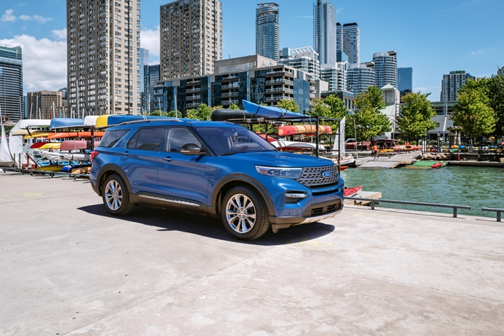2020 Explorer Limited Hybrid with twenty inch hand polished aluminum wheels parked in front of a rack of kayaks