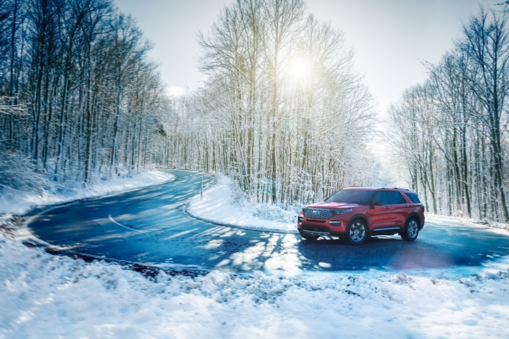 Explorer Platinum in Rapid Red driving around a curve in snowy conditions