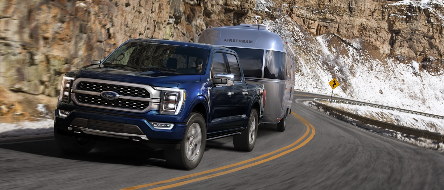 A 2021 Ford F one fifty being driven on a highway near a cliff towing a trailer