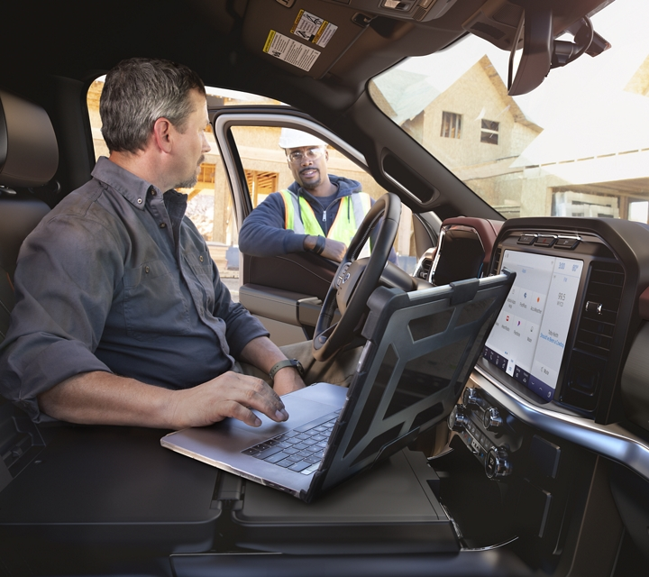 A man using a laptop on the centre console worktable in a 2021 Ford F one fifty
