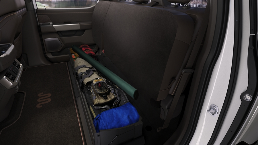 A 2021 Ford F one fifty interior with the back seats folded up to make space for camping gear under the seat